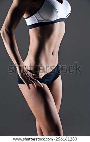 closeup studio shot of trained female body, fitness model abs - stock photo