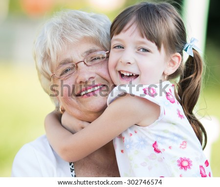 Closeup summer portrait of happy grandmother with granddaughter outdoors - stock photo