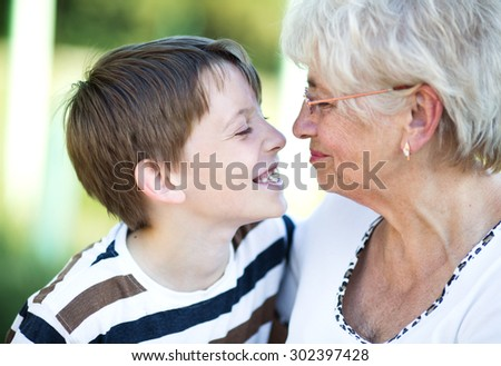 Closeup summer portrait of happy grandmother with grandson outdoors - stock photo