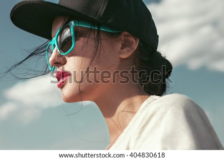 Closeup summer sunny outdoors lifestyle fashion portrait of young stylish hipster girl in sunglasses and black cap. Sky background. - stock photo