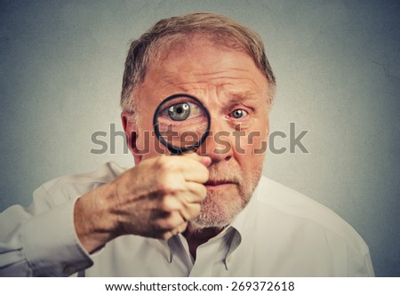Closeup surprised man looking through a magnifying glass - stock photo