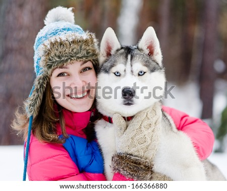 closeup teen girl embracing cute dog in winter park