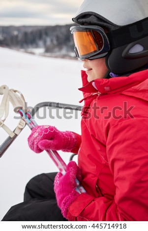 Closeup teenage girl equipped for skiing moves on cableway at ski resort. - stock photo