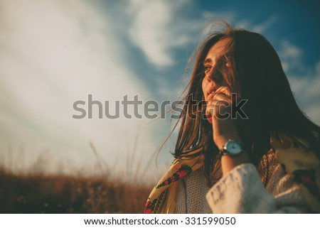 Closeup teenage girl looking into the distance on autumn cold windy day. Handsome young woman wearing warm sweater thinking and hesitating on sky background. - stock photo