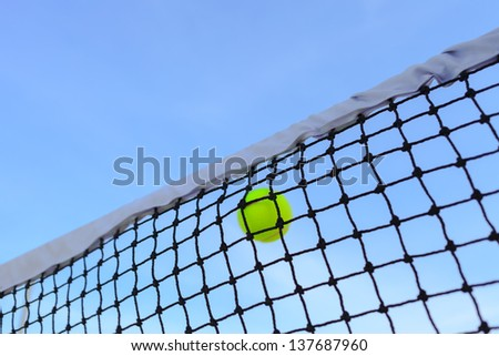 Closeup tennis net and ball with blue sky