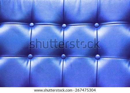 Closeup texture of vintage blue leather sofa with shadow and light . - stock photo