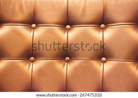 Closeup texture of vintage brown leather sofa with shadow and light . - stock photo