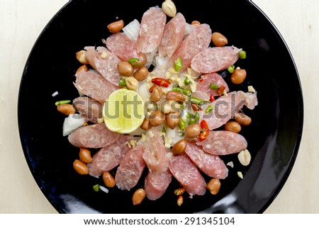 Closeup Thai sour pork sausage salad in black plate - stock photo