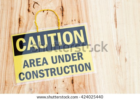closeup the sign Caution area under construction on wood background - stock photo