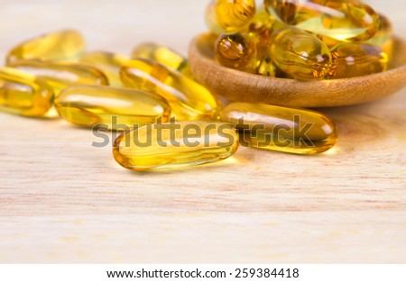 Closeup the yellow soft gelatin supplement fish oil capsule on wooden plate - stock photo