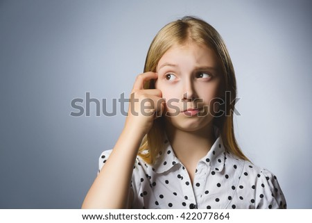 Closeup Thoughtful Young girl Looking Up with Hand on Face Against Gray Background - stock photo