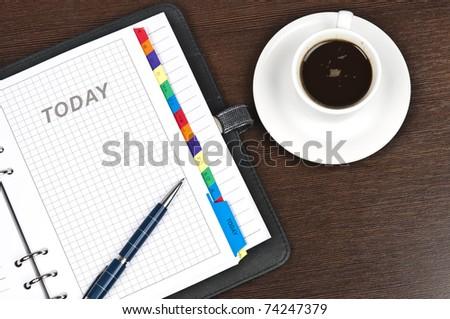 Closeup to agenda and coffee - stock photo