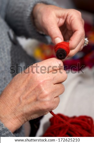 Closeup to craftsman's hand reeling thread to bobbin - stock photo