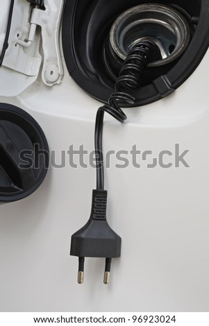 Closeup to electric spring cord detached from open petrol tank of white car, concept of converting oil fuel to environment friendly electric powered cars - stock photo