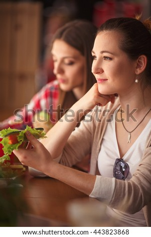 Closeup toned image of beautiful women spending free time in cafe or restaurant. Happy lady holding vegetarian dish and smiling. - stock photo
