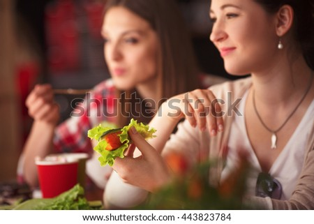 Closeup toned image of happy lady holding vegetarian dish and smiling. Beautiful women spending free time in cafe or restaurant. - stock photo