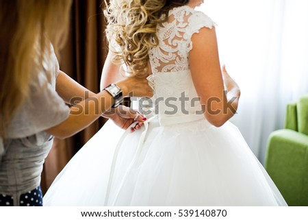 Closeup toned photo of beautiful bride tying up her wedding dress