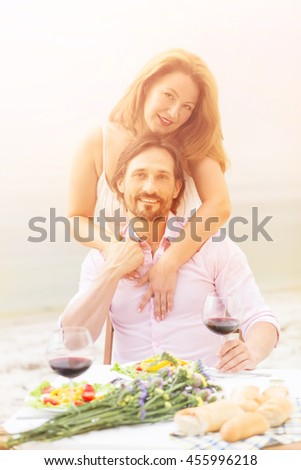 Closeup toned picture of happy couple relaxing in restaurant or cafe by sea. Beautiful red-haired woman hugging her husband isolated on sea.