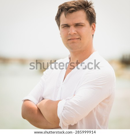 Closeup toned portrait of handsome man in white shirt with hands crossed relaxing on the beach