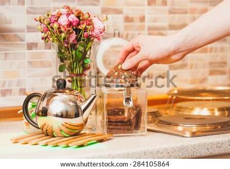 Closeup toned shot of man taking cookies out of glass jar at kitchen - stock photo