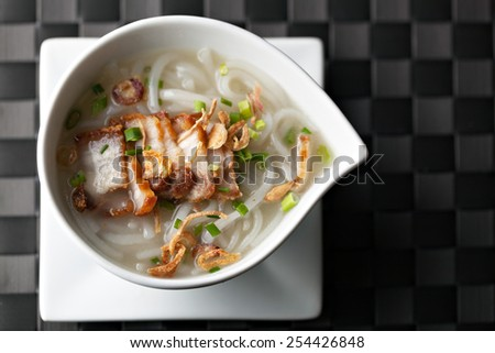 Closeup top down view of Thai style crispy pork rice noodle soup in a bowl with copy space. - stock photo