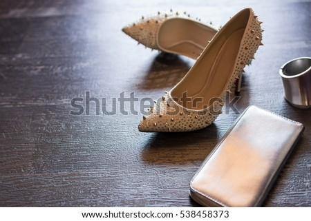 Closeup top view image of fashionable women's shoes aside accessories on a dark wooden background. Copy space