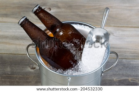 Closeup top view of fresh bottled beer sitting inside metal bucket filled with crushed iced and rustic wood in background  - stock photo