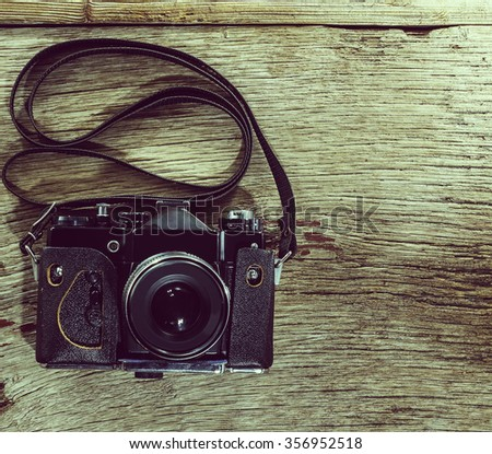closeup. top view. Retro film photo camera on the wooden background.