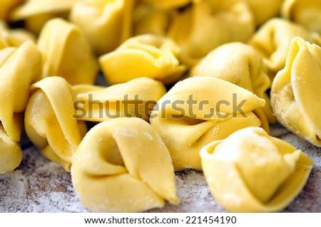 Closeup tortellini on wooden table - stock photo