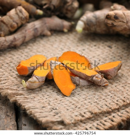 Closeup Turmeric slice on wooden background.Turmeric roots. - stock photo