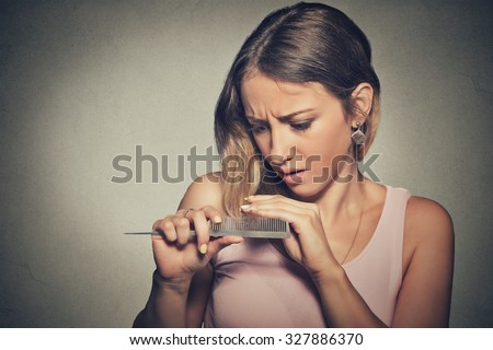 Closeup unhappy frustrated young woman surprised she is losing hair, noticed split ends receding hairline. Gray background. Human face expression emotion. Beauty hairstyle concept  - stock photo
