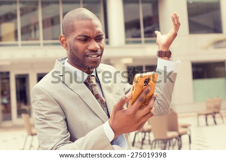 Closeup unhappy young man in suit talking texting on cellphone outdoors. Negative human face expression  - stock photo