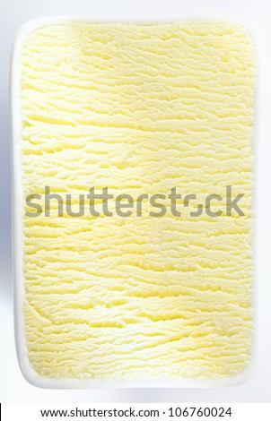 Closeup vertical background texture of a tub of lemon sorbet or vanilla icecream with a shadowed ripple running through the centre - stock photo