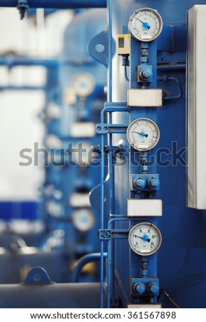Closeup vertical image of barometers at a brewery industrial plant.
