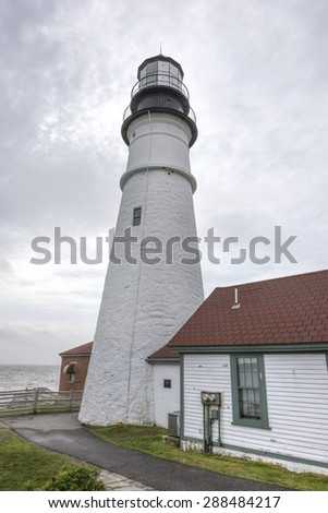 Closeup vertical shot of exterior of tower of Portland Head Light lighthouse overlooking ocean on Cape Elizabeth in Maine
