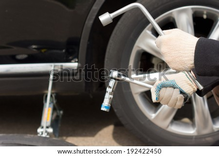 Closeup vie of the gloved hands of a man changing the tire on his vehicle following a puncture holding the wheel spanner and a socket wrench to loosen the nuts - stock photo