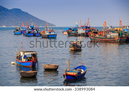 closeup Vietnamese colourful fishing boats in tranquil azure sea against green hilly island - stock photo
