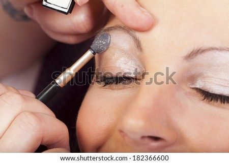 Closeup view Beautician applying eyeshadow cosmetic on the lid