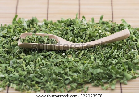 Closeup view focus on shredded pandan leaf in a bamboo spoon with more leaves and bamboo mat as background. The leaf is processed to use as herbal tea for its sweet fragrance and medicinal benefits. - stock photo