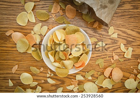 Closeup view from above of colorful veggie potato, tomato, spinach chips on a white plate and brown paper bag with greasy spots stains, on a wooden table - stock photo