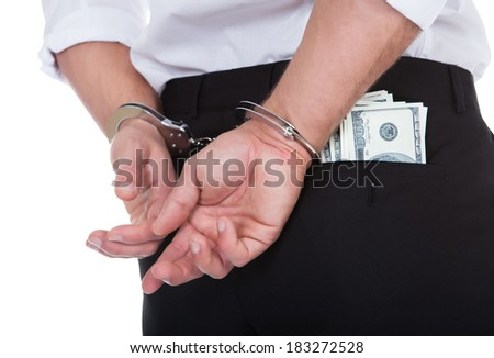 Closeup view from behind of a man in handcuffs with dollar banknotes in his pocket conceptual of crime and corruption with a bribe  the loot or a payoff - stock photo