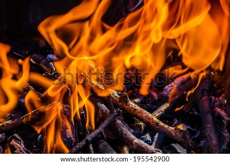 Closeup view of a bonfire flames and burning firewood. The comfort of warmth and security in the country, the dangerous thing in the city - stock photo