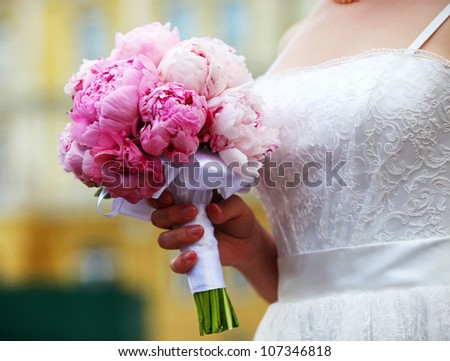 Closeup view of a bride holding bouquet of peonies - stock photo
