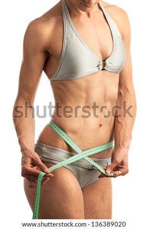 Closeup view of a fitness young woman with a measuring tape