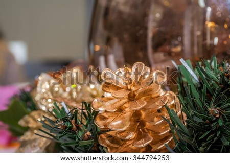 Closeup view of a golden-colored pine cone Christmas table ornament.