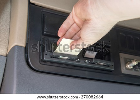 Closeup view of a hand of truck driver who inserts  tachograph card to the device inside the truck cab. - stock photo