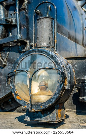 Closeup view of a headlight of the ancient steam locomotive. Petroleum lamp and a metal reflector inside the metal cage. Black boiler in the background. Vertical, portrait orientation photography - stock photo