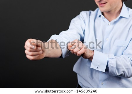 Closeup view of a man rolling up his shirtsleeves against a dark background - stock photo