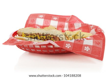 Closeup view of a plastic basket containing a hot dog on a bun with potato chips.  Focus on hot dog.  On a white background.