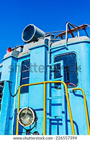 Closeup view of a service electrical railroad engine of blue color against the background of clear blue sky. Transport technology of the past. Vertical, portrait orientation photography - stock photo